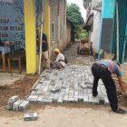 Foto: Pekerja sedang memasang paving block.