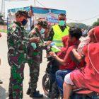 Personil Koramil 01 Teluknaga membagikan masker kepada pengguna jalan dan melakukan pemantauan PPKM di jalur menuju wisata pantai Tanjung Pasir. (dok. infotangerang.co.id)